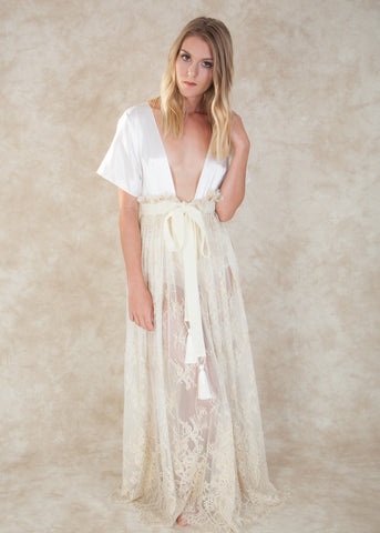 By Amoralle. The Lorraine Robe is crafted with luxurious white silk and exquisite ivory lace, finished off with a velvet statement belt with playful tassels at the ends. A piece to be treasured forever, the Lorraine Robe is an irresistible choice. Available at Koki Intimi.