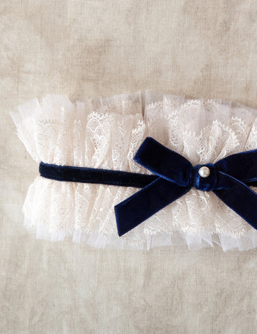 "By Amoralle. The Ebele Garter is a frilly but classic choice. It is made with a beautiful ivory lace laid over a tulle base, accented with a rich sapphire color velvet ribbon and finished off with an elegant white pearl. This an excellent choice for ""something new"" and ""something blue."" Available Koki Intimi."