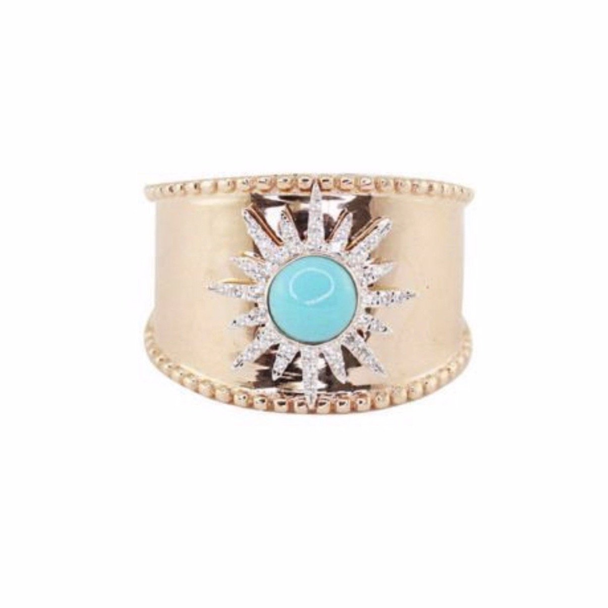 Large gold ring with crystal starburst around a blue stone.