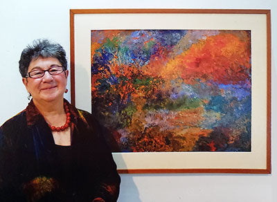 Marsha Heller in front of one of her paintings