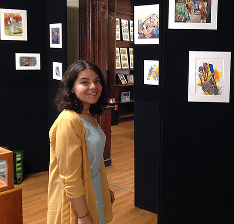 Michaela standing in front of her art at the Hoboken Public Library