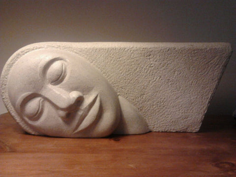 White sculpture of stone of head with resting face and hair horizontally extended