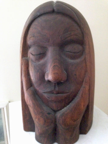 Brown scuplture of a head with closed eyes resting on two hands