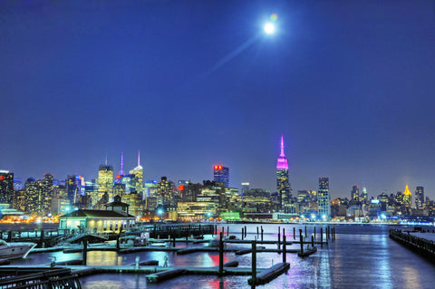 Photograph of a NYC cityscape at night with moon overhead taken from New Jersey piers