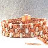 Copper bracelet with three rows of rectangular green stones