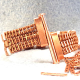 Copper bracelet with three rows of rectangular green stones unclasped