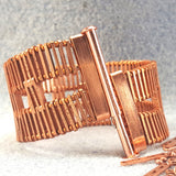 Photo of a broad copper bracelet unclasped
