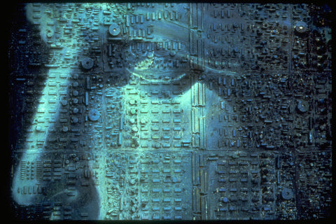 Print with circuitboard texture of closeup of the statue of liberties face only showing eye and nose in blueish gray