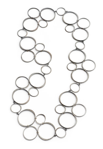 Many different shaped silver circles making up a necklace