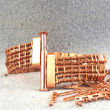 Copper bracelet with one row of rectangular green stones unclasped