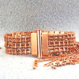 Copper bracelet with one row of rectangular green stones with clasp