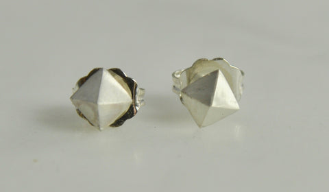 Photo of pyramid-shaped silver earings on surface