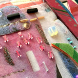 Detail of abstract wall sculpture made in collage format with various materials mostly in pink