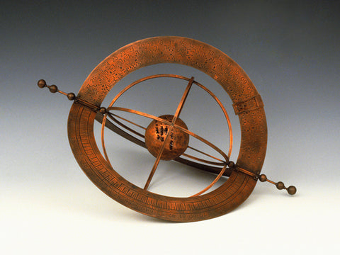 Sculpture in copper of sphere with multiple rings wrapped around an axis