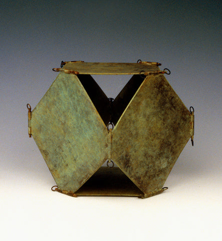 Metal sculpture of cube made up of open diamond-shaped sides hinged together