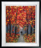 Pressed wool and silk fibers of a silouette of a person walking in an autumn woods with leaves of yellows and reds in a white matte and black frame