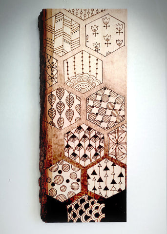 Vertical wall-mounted birch with monochromatic burned design of multiple designs within a pattern of hexagons