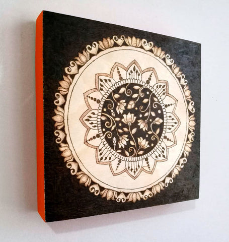 Decorative circle drawing burned on square wood panel