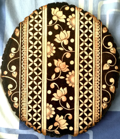 Vertical floral lattice drawing burned onto oval wood with rough edges from bark
