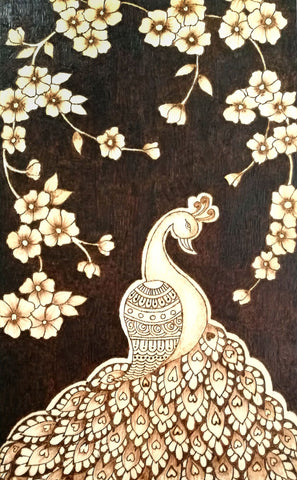 Decorative drawing of a peacock under hanging brances of flowers burned on wood panel