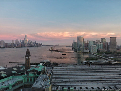 Aerial scene of lower Hoboken's waterfront and Jersey City in front of lower Manhattan, NYC