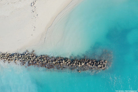 Aerial view of a horizontal row of rocks in blue-green water