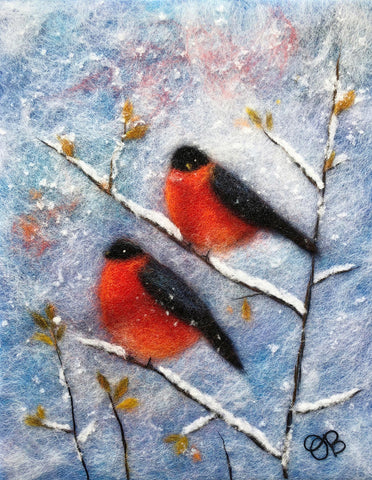 Fibers make up two red birds with black heads and wings perched on snow covered branches with tiny earthy leaves on snowy blue background