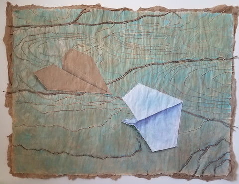 Tan and white paper airplanes on brown paper with rough edges and applied yarn and thread making rivers and contours