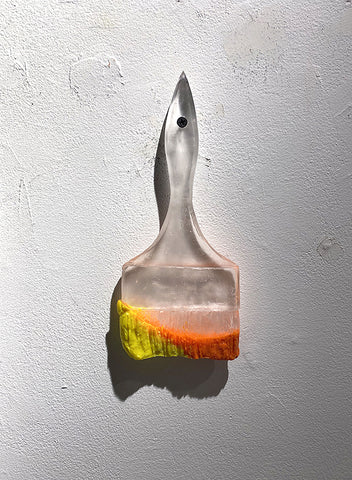 Hanging clear-to-frosted glass scupture of a wide paintbrush with yellow to red paint on tip