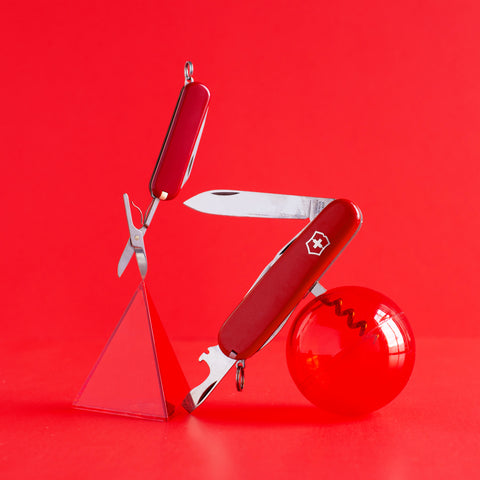 Two swiss army knives positioned into a sculpture with a ball and pyramid on a solid red background