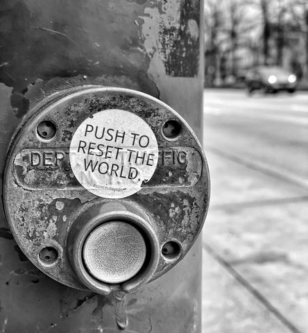"Black and white photo of crosswalk button with sticker above that reads, ""PUSH TO RESET THE WORLD."""