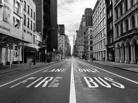 Black and white photo of empty street in NYC with LANE ONLY FIRE BUS on road