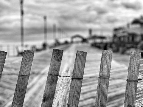Black and white photo of a close-up of a fence in front of a blurred boardwalk in the distance