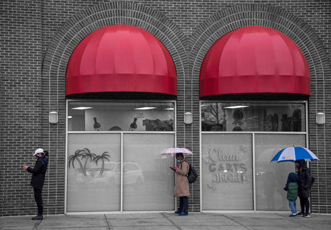 Color photograph of four people in line spaced apart two holding umbrellas under red awnings