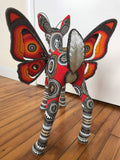 Backside of beaded sculpture of fantastic winged-deer creature in mostly reds and oranges