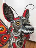 Face of beaded sculpture of fantastic winged-deer creature in mostly reds and oranges