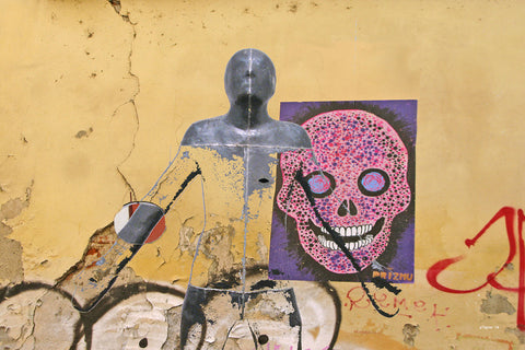Photomontage with humanoid figure center in front of a yellow wall with skull poster
