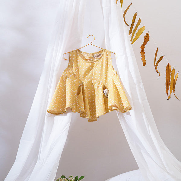 A stylishly cut flared top with invisible pockets for your little one to hide her precious treasures in. Made with sustainably grown cotton fabric. Herbal dyed with natural shell buttons at the back