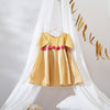 Gorgeous party or vintage flower girl wedding dress made with sustainably grown cotton fabric and herbal dye. Perfect for your little angel to impress and play in. Top of dress is made with soft khadi. The bottom is from sustainably grown cotton in yellow polka dots. Herbal dyed with natural wood buttons at the back