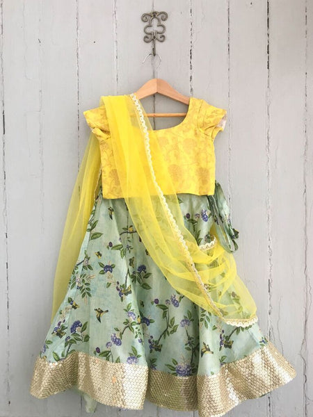 Tusser silk lengha with cornflower blue floral design. Contrasting jacquard top with elasticated waist for extra comfort. A yellow chiffon dupatta with border trim completes the look