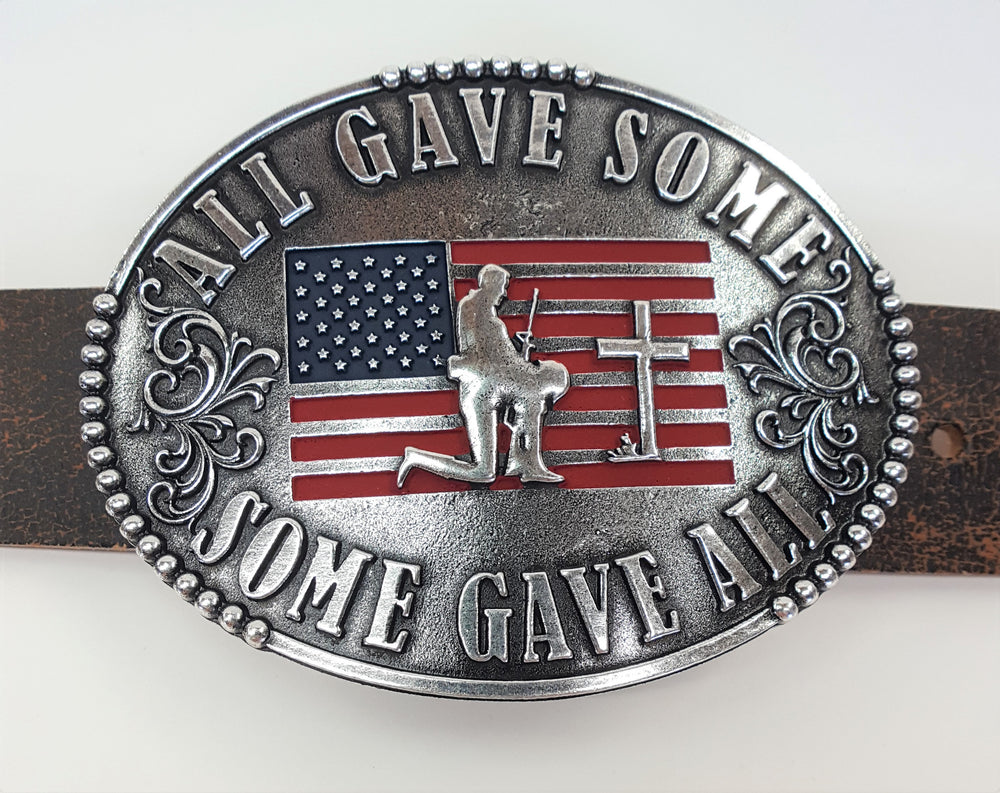 "All Gave Some Some Gave All Buckle oval plate style belt buckle with American Flag inlay under kneeling soldier and cross. All Gave Some, Some Gave All imprinted around edges of buckle and scroll design on either side of wording. Available in our shop just outside Nashville in Smyrna, TN as well as on this website.  Made by AndWest in Mexico. Dimensions are 3 1/4"" by 4 1/4"", pictured on crackle finish brown leather belt."