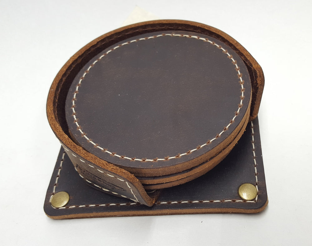 "Handmade leather drink coasters with holder.  Made just outside Nashville in Smyrna, TN. Coasters come in set of 6 round 3 1/2"" diameter pieces shown with stitching around the edges. Shown in brown cowhide. Corral square piece of leather with rounded edges and rounded retaining edge approx. 1' tall riveted in place to provide secure placement of coasters when not in use."
