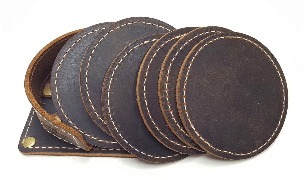 "Handmade leather drink coasters with holder.  Made just outside Nashville in Smyrna, TN. Coasters come in set of 6 round 3 1/2"" diameter pieces shown with stitching around the edges. Shown in brown cowhide. Corral square piece of leather with rounded edges and rounded retaining edge approx. 1' tall riveted in place to provide secure placement of coasters when not in use. Coasters shown spreading out of corral."