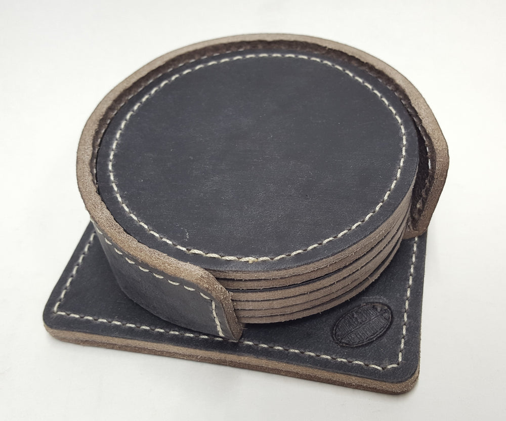"Handmade leather drink coasters with holder.  Made just outside Nashville in Smyrna, TN. Coasters come in set of 6 round 3 1/2"" diameter pieces shown with stitching around the edges. Shown in black cowhide. Corral square piece of leather with rounded edges and rounded retaining edge approx. 1' tall riveted in place to provide secure placement of coasters when not in use."