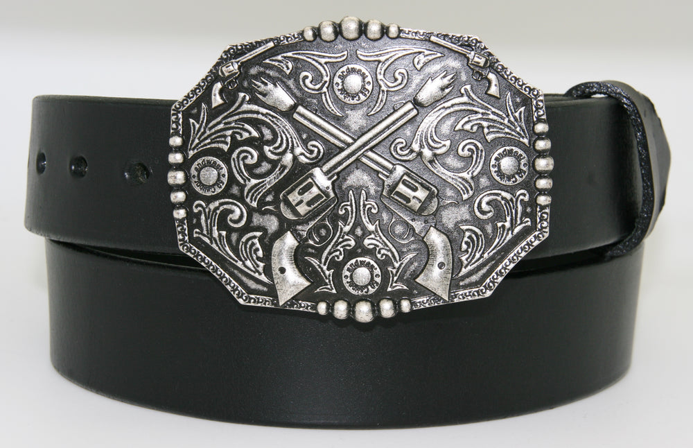 "Crossed pistols buckle pictured on black belt-This antique silver colored buckle by AndWest features a pair of crossed pistols centered on the oval shaped buckle with flattened sides. It also features 50 caliber shell end replicas within the Western scroll background design.  Fits belts up to 1 1/2"" wide, dimensions are 3"" tall by 4"" wide.  Available in our online store as well as the retail shop in Smyrna, TN, just outside of Nashville.  This buckle is made in Mexico."