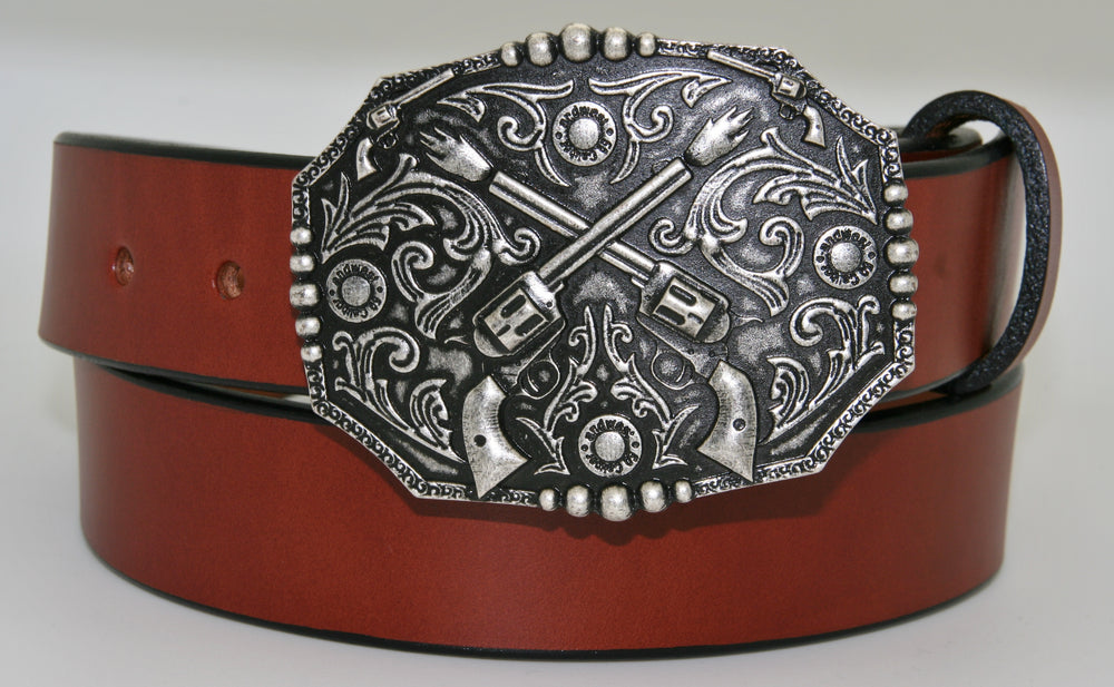 "Crossed pistols buckle pictured on brown belt-This antique silver colored buckle by AndWest features a pair of crossed pistols centered on the oval shaped buckle with flattened sides. It also features 50 caliber shell end replicas within the Western scroll background design.  Fits belts up to 1 1/2"" wide, dimensions are 3"" tall by 4"" wide.  Available in our online store as well as the retail shop in Smyrna, TN, just outside of Nashville.  This buckle is made in Mexico."