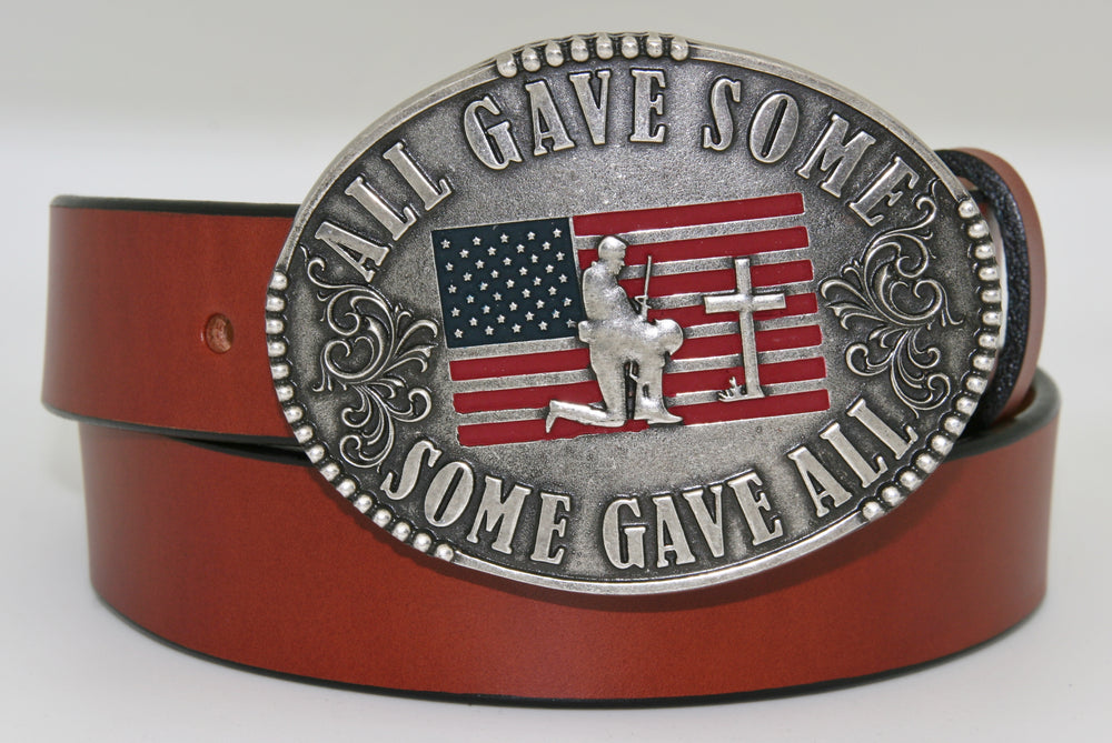 "All Gave Some Some Gave All Buckle oval plate style belt buckle with American Flag inlay under kneeling soldier and cross. All Gave Some, Some Gave All imprinted around edges of buckle and scroll design on either side of wording. Available in our shop just outside Nashville in Smyrna, TN as well as on this website.  Made by AndWest in Mexico. Dimensions are 3 1/4"" by 4 1/4"", pictured on sturdy brown leather belt, also available from this shop."