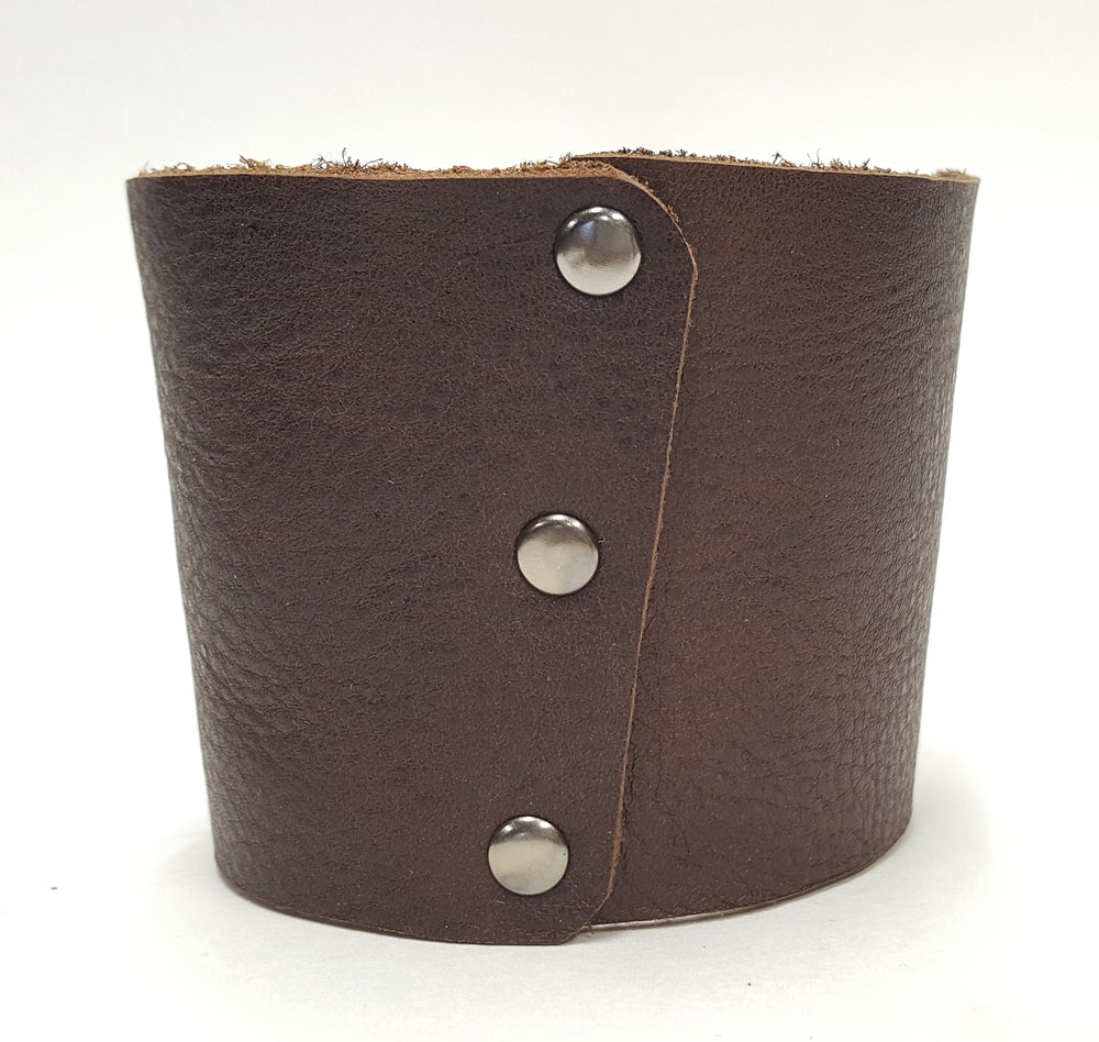 Brown leather coffee cup sleeve with silver colored rivets along connecting edge. Made from brown cowhide in the shop just outside Nashville in Smyrna, TN