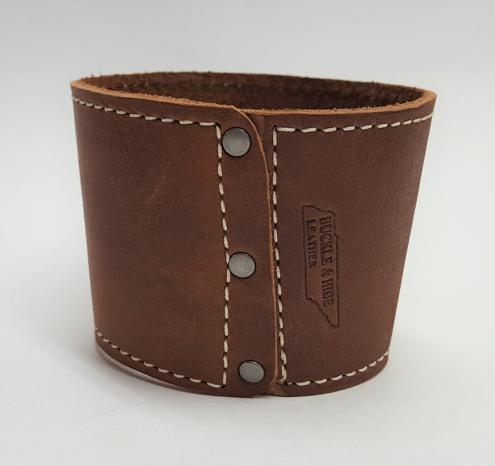Brown leather coffee cup sleeve with silver colored rivets along connecting edge. Edges stitched with white contrasting thread. Made from brown cowhide in the shop just outside Nashville in Smyrna, TN