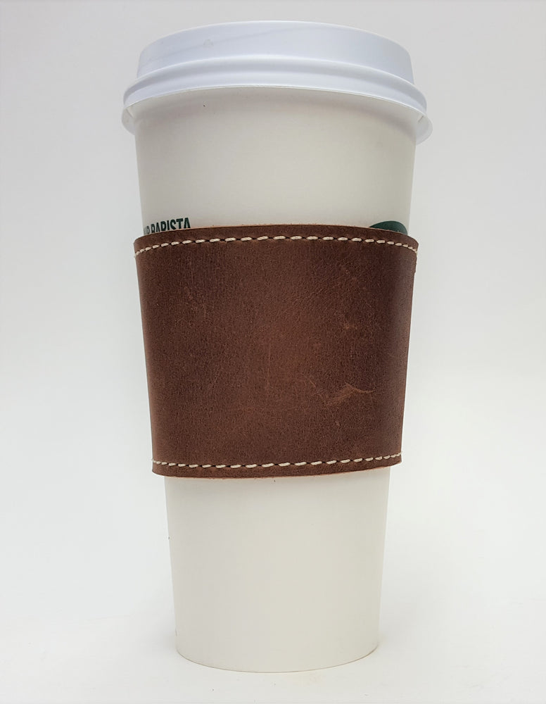 Brown leather coffee cup sleeve with silver colored rivets along connecting edge. Edges stitched with white contrasting thread. View pictured with coffee to go cup. Made from brown cowhide in the shop just outside Nashville in Smyrna, TN